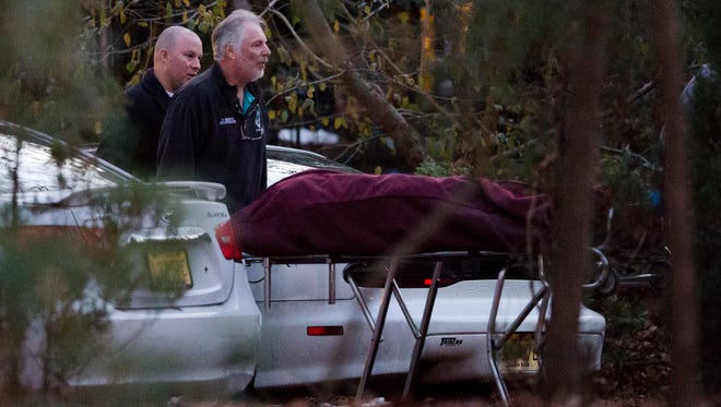 One of two bodies are removed from the scene of a shooting Thursday, Nov. 20, 2014, in Tabernacle, N.J. The shooting left two children dead and a woman and another child wounded, state police said Thursday. (AP Photo/Matt Rourke)