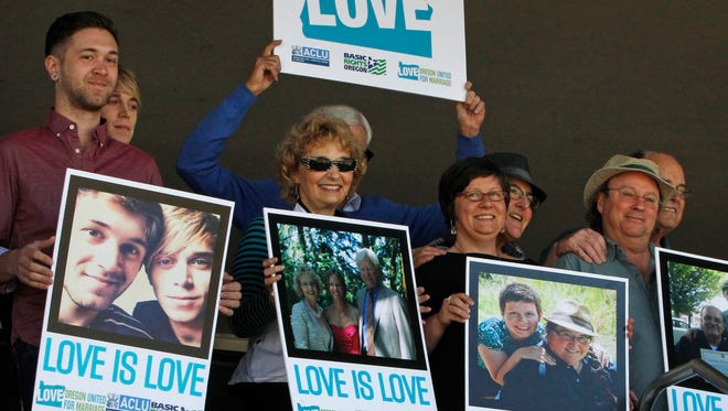 Supporters of same-sex marriage hold photos of themselves and their family members or partners on the steps of the Wayne L Morse U.S. Courthouse Wednesday, May 14, 2014, in Eugene, Ore. A federal judge will hear arguments Wednesday about whether a national group can defend Oregon's ban on same-sex marriage because the state's attorney general has refused to do so.