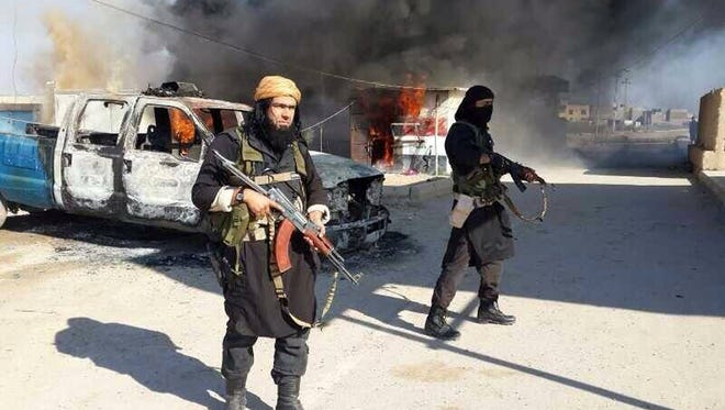A senior member of the al-Qaeda-linked Islamic State of Iraq and the Levant (ISIL) next to a burning police vehicle in Iraq's Anbar Province.