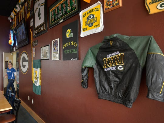 A Super Bowl XXXI champion Green Bay Packers coat hangs on the Blue Line Sports Bar & Grill's Packer wall Monday, Feb. 1, 2016 in Sartell. Owner Scott Widor, like most sports bar owners, sees an uptick in business during the Super Bowl, but he says it'd actually be better if the games were moved to a Saturday.