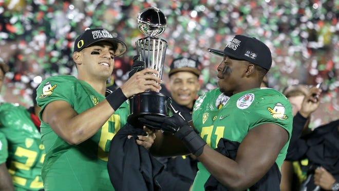 Oregon quarterback Marcus Mariota (8) celebrates with teammate Tony Washington while holding the Rose Bowl trophy after defeating Florida State on Thursday, Jan. 1, 2015, Pasadena, Calif.