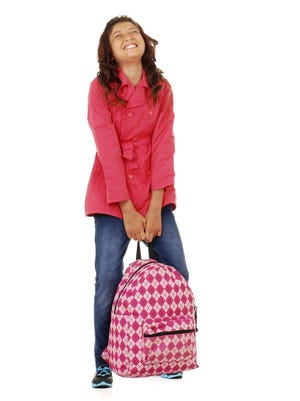 A girl struggles to lift a heavy backpack. Putting too many items in a backpack or wearing it improperly can cause pain and damage.
