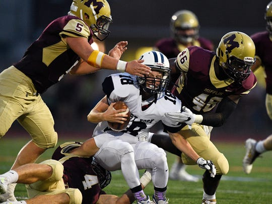 West York's Corey Wise is swarmed by three Governor Mifflin defenders during a 2017 game. Governor Mifflin is one of 13 Berks County schools slated to become associate football members of the Lancaster-Lebanon League in 2022.