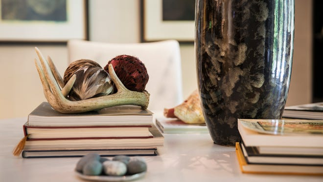 Antlers, stones and feather-covered spheres are grouped with books and a glass vase to bring together a natural and nature-inspired look.