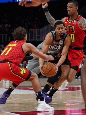 Brooklyn Nets Spencer Dinwiddie (26) tries to drive past Atlanta Hawks Trae Young (11) John Collins in the first half of an NBA basketball game Friday, Feb. 28, 2020, in Atlanta.