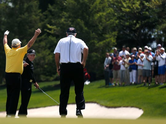 Jack Nicklaus raises his arms after making a putt on