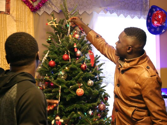 Bonaventure Tadjim, left, and Placide Kagde hanging ornaments on the family's new tree.