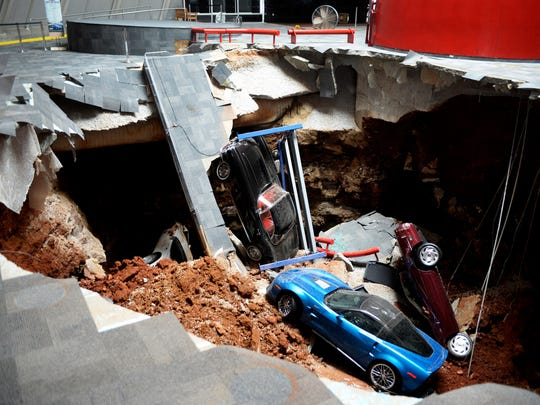 In this Wednesday, Feb. 12, 2014 photo, cars lie in a sinkhole that opened up at the Skydome showroom in the National Corvette Museum in Bowling Green, Ky.