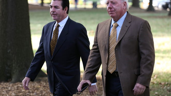 John Schnatter, left, CEO of Papa John's Pizza, arrives for a UofL for Board of Trustees meeting escorted by Buddy Dumeyer outside Grawemeyer Hall.