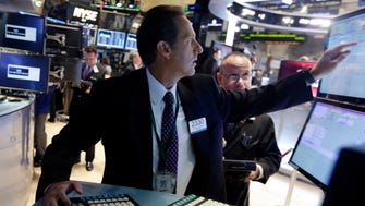 Specialist Glenn Carell, center, works at his post on the floor of the New York Stock Exchange.