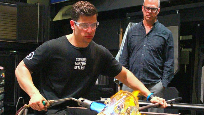 Glass artist Harry Allen, background, watches a museum staffer work during a public glass making demonstration Friday at the Corning Museum of Glass.