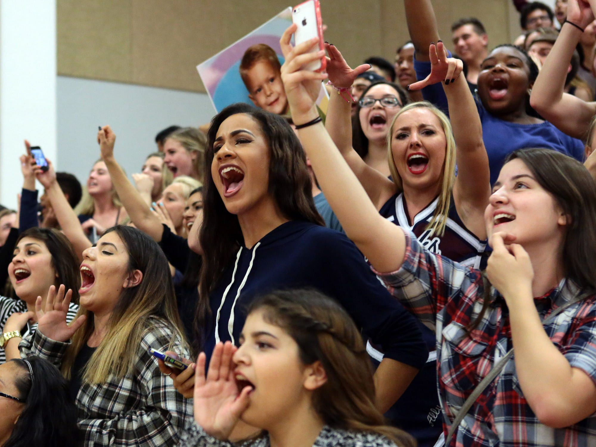 La Quinta fans erupt and one (at right) takes a selfie as the Blackhawks pull ahead in the closing minutes of their boys' basketball game at Palm Desert on Thursday, February 12, 2015 to win this season's Desert Valley League title.