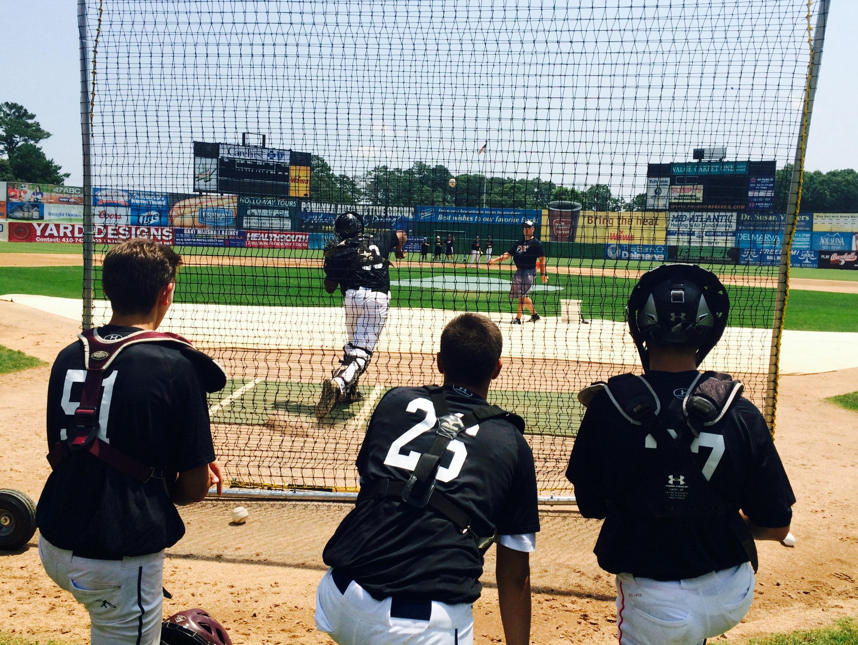 Players watch the catcher's drill at the Eastern Shore Showcase, a chance for rising prep stars to show off their talents.