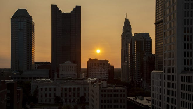 The sun sets behind the Columbus skyline on Tuesday. Due to western wildfires, the sky has appeared hazier this week at sunrise and sunset.