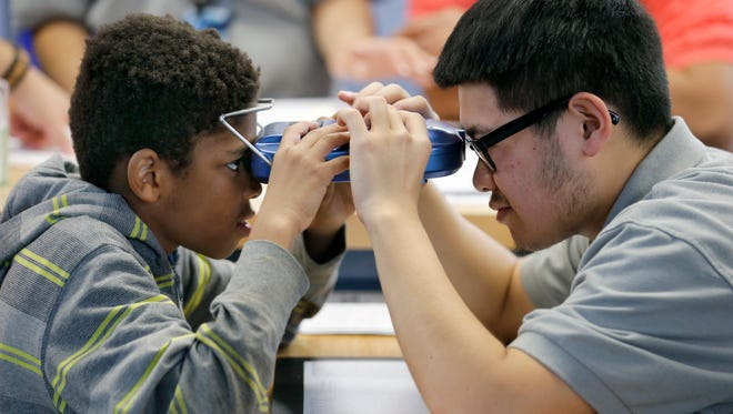 Marquise Brooks, a fourth-grader from School No. 8, gets his eyes checked by East High School senior Kevin Lin, who has been with the optician training program for two years.
