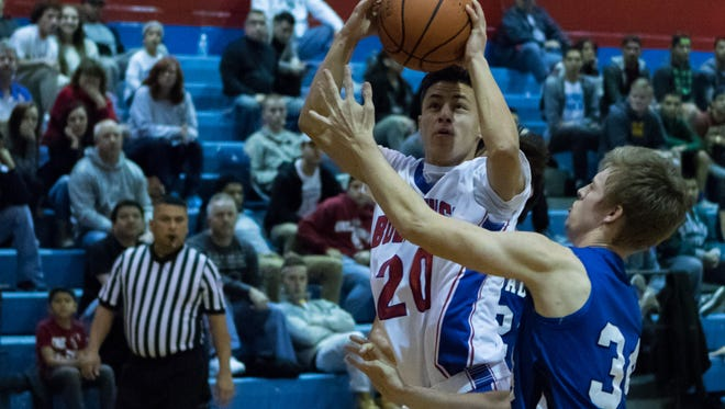 Las Cruces High's Isaiah Tellez (20) goes up for the basket against Carlsbad's Daniel Miller Friday night at Las Cruces High School.