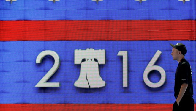 A worker walks past a video display during preparations for the 2016 Democratic National Convention on Friday.
