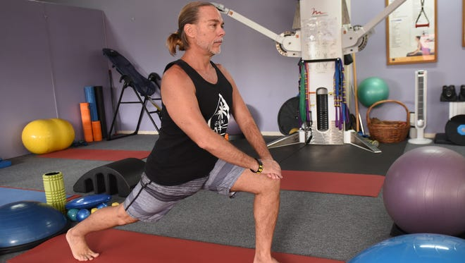 Certified Personal Trainer Pepe Laflamme perform a version of a runner's stretch exercise, without the use of any special equipment, during a demonstration at his NuForm Pilates Fusion & Personal Training studio in Tamuning on Friday, Oct, 13, 2017. To start the exercise, Laflamme places one leg stretched rearward while the knee of the other is bent at a right angle in front of the body, hands resting on forward knee for support and toes of both feet are pointed forward, as shown.
