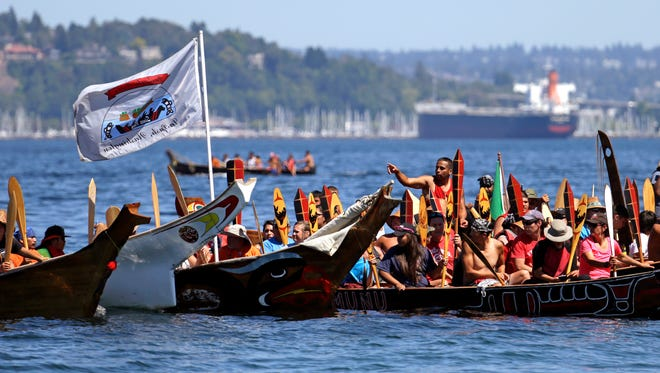 Tribal canoes raft-up before heading to their arrival on a nearby beach during an annual journey Wednesday, July 27, 2016, in Seattle.  Dozens of tribal canoes were arriving at Alki Beach in Seattle as part of an annual Native American celebration. Members of the Muckleshoot Tribe greeted the boats Wednesday afternoon as part of the 2016 Paddle to Nisqually. (AP Photo/Elaine Thompson)