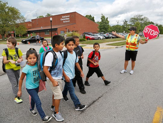 Crossing guard Max Cady directs youngsters across Kossuth
