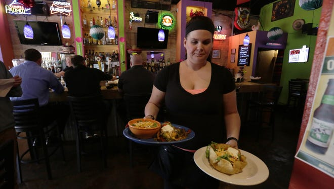 Jessica Wiseman, a server at South of the Border Restaurante & Cantina, brings out a couple dishes from the kitchen Wednesday, May 3, 2017, at the South Main Street eatery. The restaurant will be ready and open for business on Cinco de Mayo. This and other Mexican restaurants in Oshkosh are preparing for hundreds of patrons are expected to pass through their doors for the holiday, which falls on a Friday this year.