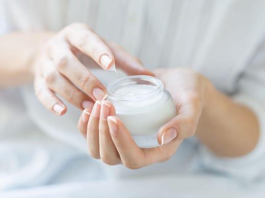 Beautiful woman hands applying moisturizer