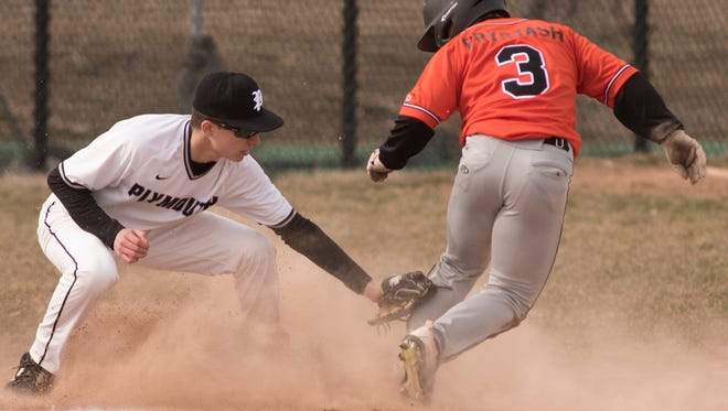 Northville base-runner Nicholas Prystash (3) is safe ahead of the tag by Plymouth third baseman Logan Dziadzio.