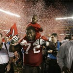 Roman Oben carries his son after Tampa Bay wins the Super Bowl in 2003.