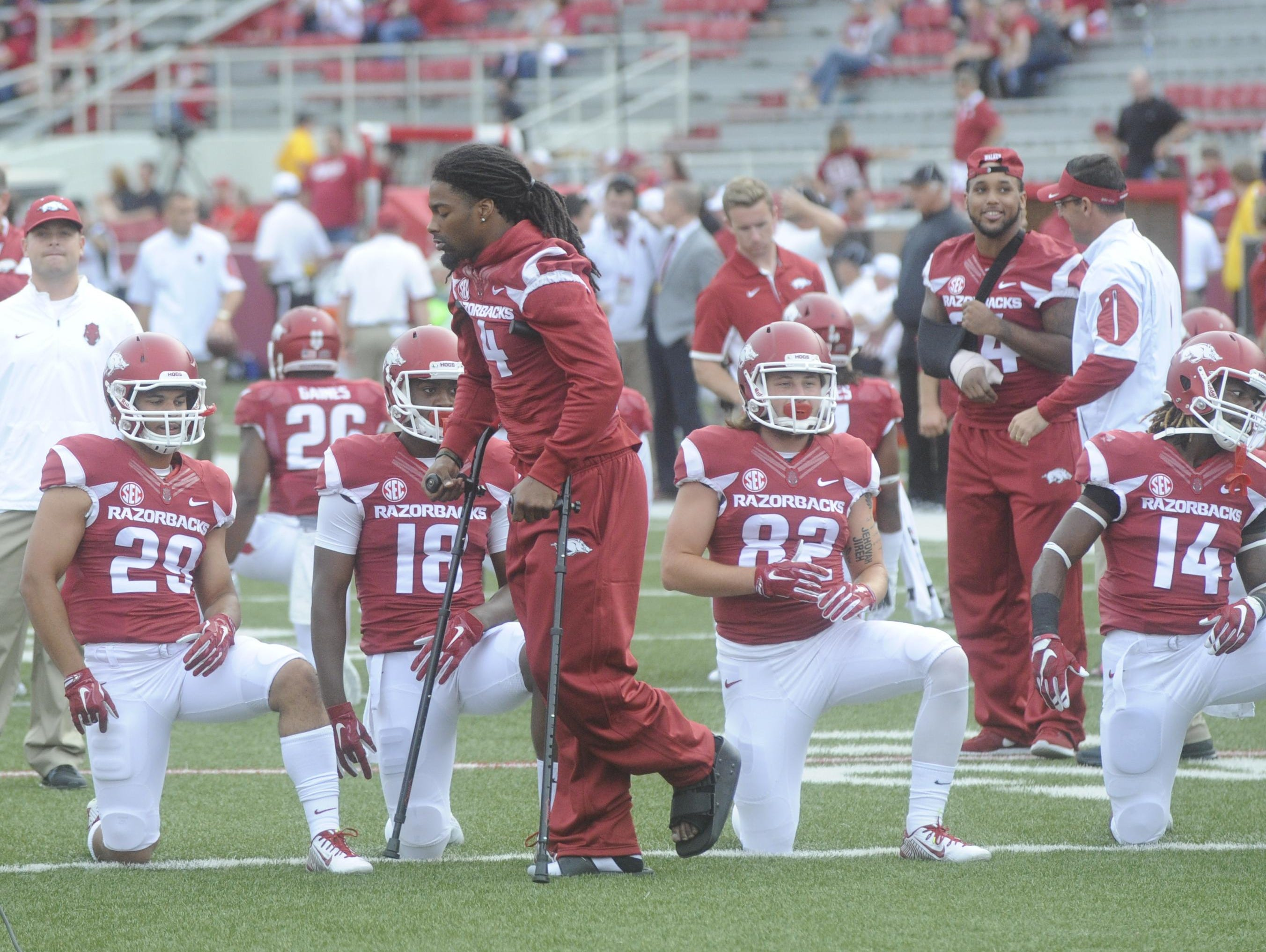 Arkansas' Keon Hatcher (4) joins teammates during pre-game warm-ups before playing Texas Tech on Saturday in Fayetteville. Hatcher is just one of several Razorbacks starters to suffer significant injury this season.