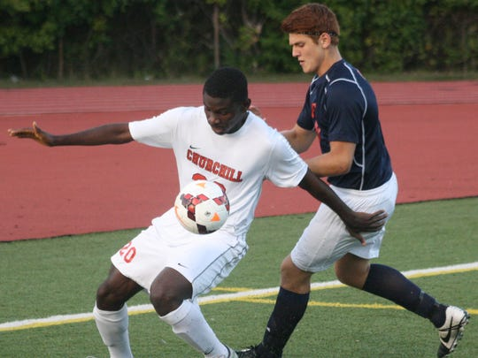 Churchill's Uthman Babatunde shields Patriot Nathan Iacoban from the ball.