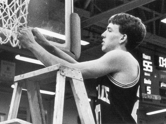 Tony Etchison of Noblesville, takes the first cut of the 1990 Carmel sectional championship net.