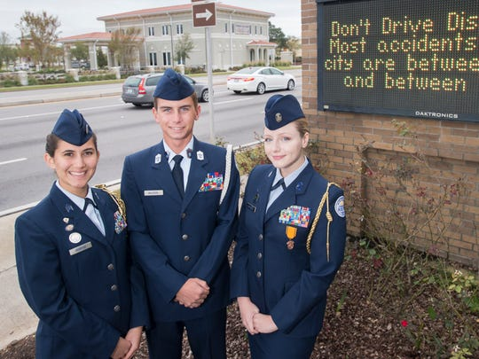 "Air Force Junior ROTC Cadet Col. Jasmaine Roberge, left to right, Cadet Chief Master Sergeant Kyle Muldoon, and Cadet Lt. Col. Grace Overholtz pose in front of the marquee sign displaying their ""Don't Drive Distracted"" message at Gulf Breeze High School on Thursday, November 9, 2017."