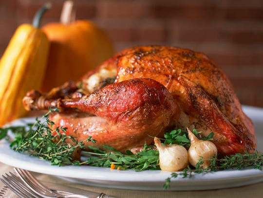 A cooked Thanksgiving turkey is plated with herbs and