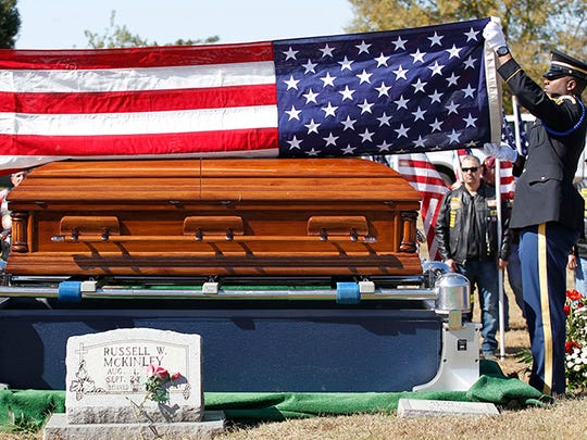 In this photo taken Oct. 20, 2015, an honor guard folds an American flag that was draped on the casket with remains of Army Cpl. George H. Mason, who fought in the Korean War and was buried near his parents in his north Mississippi hometown of Byhalia, Miss. Mason, then 19, had been missing in action since Feb. 14, 1951 near Chuam-ni, South Korea.