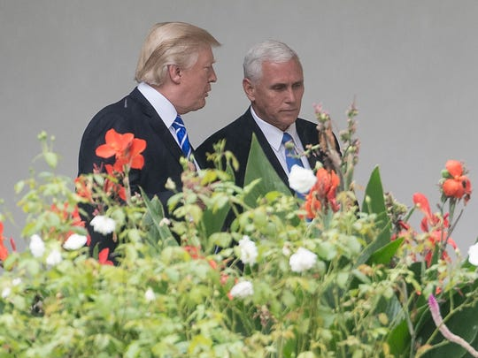 Trump speaks with Pence as they walk through the colonnade at the White House before Trump departs for North Dakota on Sept. 6, 2017.