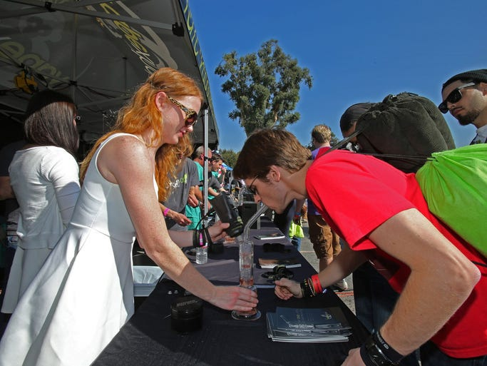 Brianne O'Neill of Nashville demonstrates the Vapexhale for a customer at the Cannabis Cup event in San Bernardino, Calif. The Los Angeles Cannabis Cup event is sponsored by High Times magazine and is one of the largest trade shows for the medical marijuana industry.