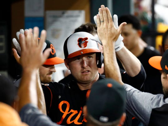Baltimore Orioles' Mark Trumbo high-fives teammates in the dugout after hitting a solo home run in the second inning of a baseball game against the Los Angeles Angels in Baltimore, Friday, Aug. 18, 2017. (AP Photo/Patrick Semansky)