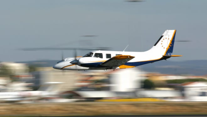 A small aircraft fly by at an airport.