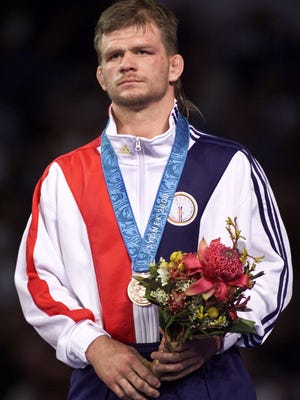 USA's Lincoln McIlravy stands on the podium wearing his bronze medal after beating Sergei Demchenko of Belarus in the 69 kg freestlye wrestling consolation at the Sydney Olympics Sunday Oct. 1, 2000.