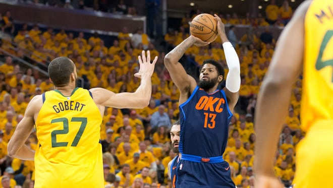 Oklahoma City Thunder forward Paul George (13) shoots the ball against Utah Jazz center Rudy Gobert (27) during the first quarter of game six of the first round of the 2018 NBA Playoffs at Vivint Smart Home Arena.