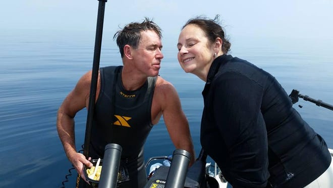 Dr. Chris Lechner and his wife, Jana, greet one another Monday on Lake Michigan, about 15 miles from shore. Jana Lechner brought her husband a meal and fresh batteries on his 80-mile swim across the Great Lake.