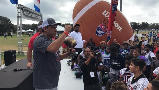 Rough Riders head coach Jake Gutierrez addresses his team of youth football players on Friday, Dec. 8, 2017 after they were awarded third place in their age category of the American Youth Football championship tourney in Kissimmee, Florida.