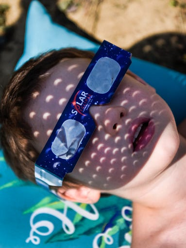 Robert Glynn, 6, stares up at the solar eclipse as