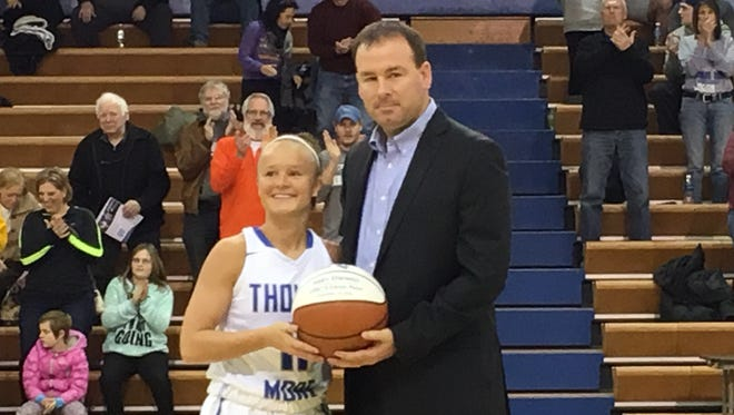 Thomas More junior Abby Owings receives her 1,000-point basketball from Saints coach Jeff Hans recently at Connor Convocation Center.