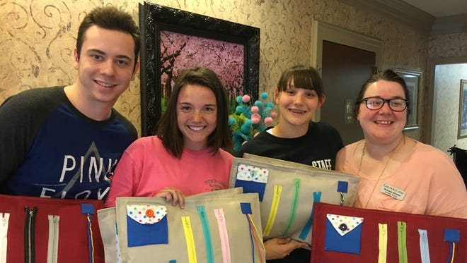 Cotter FBLA members created, designed, and donated fidget mats to the Gassville Nursing Home. Students made flat, plush pillows that can be kept in the lap of patients. Their hands can comfortably manipulate the objects on the mats, such as zippers, buttons, and sliding beads. As children are often calmed by their favorite toy or blanket or having something to do with their hands, a patient with Alzheimer's, dementia or other memory loss may also be soothed by fidget mats. FBLA members involved in the project delivered the mats to the Gassville Nursing Center recently. Shown are Dalton Orsborn, Macie Clawson, Marie Reed, and Center Director Susanna Morris.