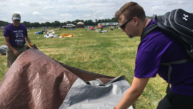Andrew Weschler of Bethany Beach (right) and Marc Lopez of Lewes fold up a tent left behind at the Firefly Music Festival campground that will be cleaned and distributed to the homeless by Code Purple of Kent County.