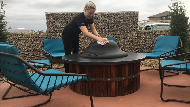Server Bobbie Jo Larsen at The Barrel House cleans off a fire pit cover in anticipation of Wednesday's opening of a new patio.