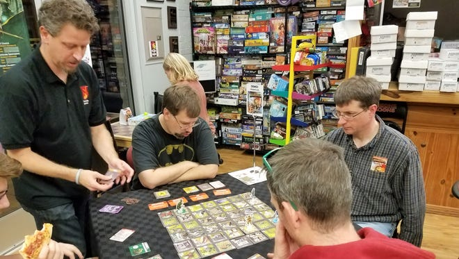 Board game designer Justin De Witt, left, shows people how to play a game he designed at The GameBoard in Sheboygan on Sept. 19.