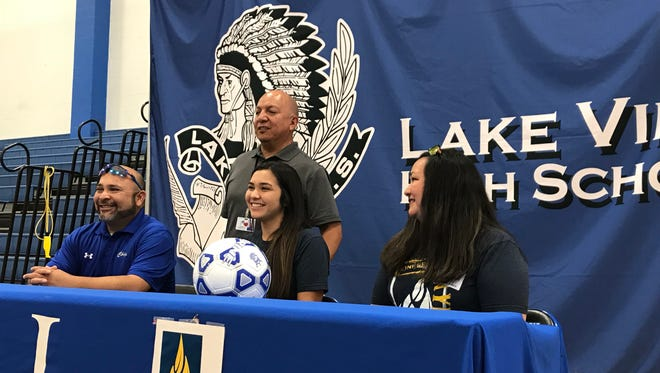 Lake View's Veronica Prieto, center, poses for photos with her coach, Henry Gonzales (standing), her father Tony, left, and mother Jessica. Prieto signed an agreement to play soccer for Wayland Baptist University on Wednesday, May 16, 2018, at Lake View High School's Ben Norton Gym.