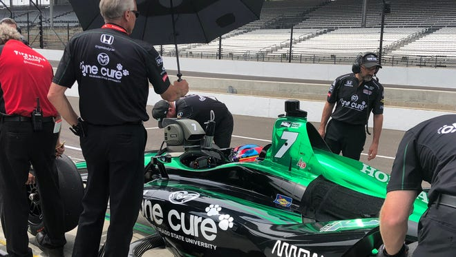 The pit crew makes adjustments to the One Cure race-car Jay Howard is driving in Sunday's Indianapolis 500 during a practice session earlier this week.